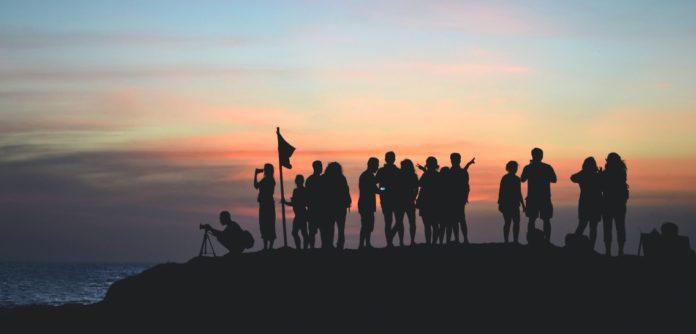 En gruppe mennesker står sammen ved havet i solnedgangen
